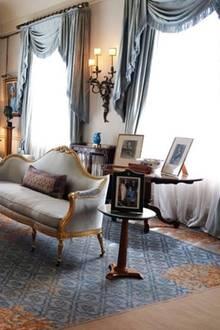Der Wohnbereich des Clarance Houses ist mit pompösen Sitzelementen und Teppichen ausgestattet. Bilder der Familien verleihen dem Raum einen wohnlichen Charakter. Gold-Elemente einen edlen Touch.