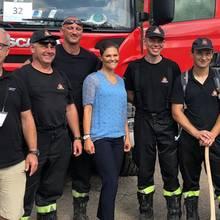 So lässig sieht man Prinzessin Victoria eher selten: Im hellblauen Chiffon-Shirt, dunkler Hose und weißen Turnschuhen posiert sie gemeinsam mit den helfenden Feuerwehrleuten aus Polen.
