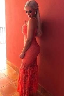 """Daniela Katzenberger setzt auf Farbe. Ihrkörperbetontes, bodenlangesSpitzenkleid mit Volant-Details ist an sich schon ein toller Blickfang. So richtig inSzene setzt die hübsche Blondine ihren Look aber erst durch eineindrucksvollesPO-sing. """"Bauch rein, Brust raus"""" schreibt sie selbst unter ihr Bild auf Instagram. Die Position von der Seite setzt nicht nurDekolleté UNDPoin den Fokus, sondern zaubert aucheine wunderbare Silhouette mit heißen Kurven."""