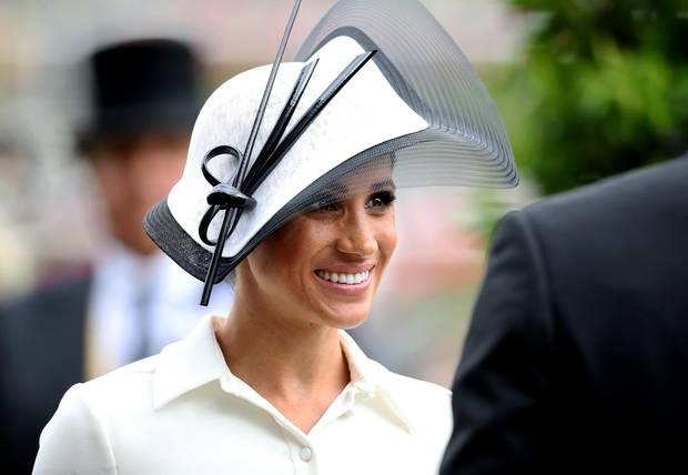 """Beim Royal Ascot Pferderennen verzaubert Herzogin Meghan in einem weißen Midikleid vonGivenchy, zu welchem sie schlichte schwarze Pumps kombiniert. Der Hut ist natürlich farblich auf das Kleid abgestimmt. Kurz: Die perfekte Wahl angesichts des strengen Dresscodes beim RoyalAscot. Der Philip Treacy Fascinator steht der jungen Herzogin ganz fantastisch.Ob Zufall oder nicht - das schwarz-weiße Outfit erinnertan jenes berühmte Ensemble, welchesAudrey Hepburn1964 beim Besuch einesPferderennensim Kultmusical """"My Fair Lady"""" trägt."""