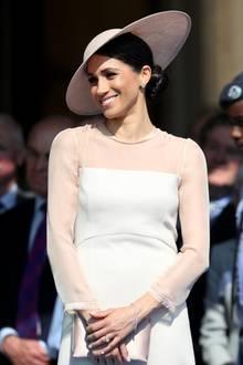 Die Hüte des irischen DesignersPhilip Treacy scheinen es der jungen Herzogin Meghan angetan zu haben. Bei einer Gartenparty trägt Meghan ein opulentes Model des Designers in einem zarten Rosa.