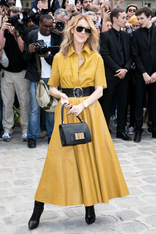 Zur Dior Haute Couture Show in Paris strahlt Céline Dion in einem femininen Lederkleid. Ihre Taille betont sie mit einem breiten, schwarzen Gürtel. Und natürlich schauen wir alle auf ihre hübsche Handtasche von Dior.