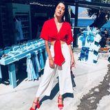 Den Urlaubs-Flair spiegelt Rebecca Mirs Outfit ganz hervorragend wieder. Die weite Culotte wirkt luftig, der Rotton ihrer Bluse und Schuhe dafür warm. Zusammen ergibt das eine kühle Brise an einem heißen Sommertag.