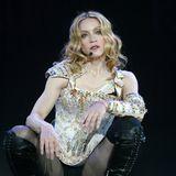 """Madonna wird 60: Mit ihrem neunten Album """"American Life"""" geht Madonna 2004 auf die """"Re-Invention"""" World-Tournee und tritt mit vergleichsweise dezenten Outfits auf die Bühne. Unter anderem performt die Sängerin in einem Look aus einem aufwendig verziertem Body, einer Netzstrumpfhose und schwarzen Overknee-Schnürstiefel."""