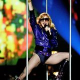 """Madonna wird 60: Mit ihrem Song """"Hung Up"""" läutet Madonna 2005 offiziell ihre Disco-Phase ein. Während der MTV Europe Music Awards in Lissabon trägt sie bei der Performance ihres neues Songs eine lilafarbene Lederjacke im Bomber-Stil und dazu farblich abgestimmte Schnürstiefel. Body und Netzstrumpfhose geben dem Look den typischen Madonna-Touch."""