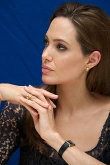"""Bei einer Konferenz trägt Angelina Jolie ihre schwarze """"Cartier Tank"""", die durch den Goldrahmen perfekt zu ihrem restlichen Goldschmuck passt."""