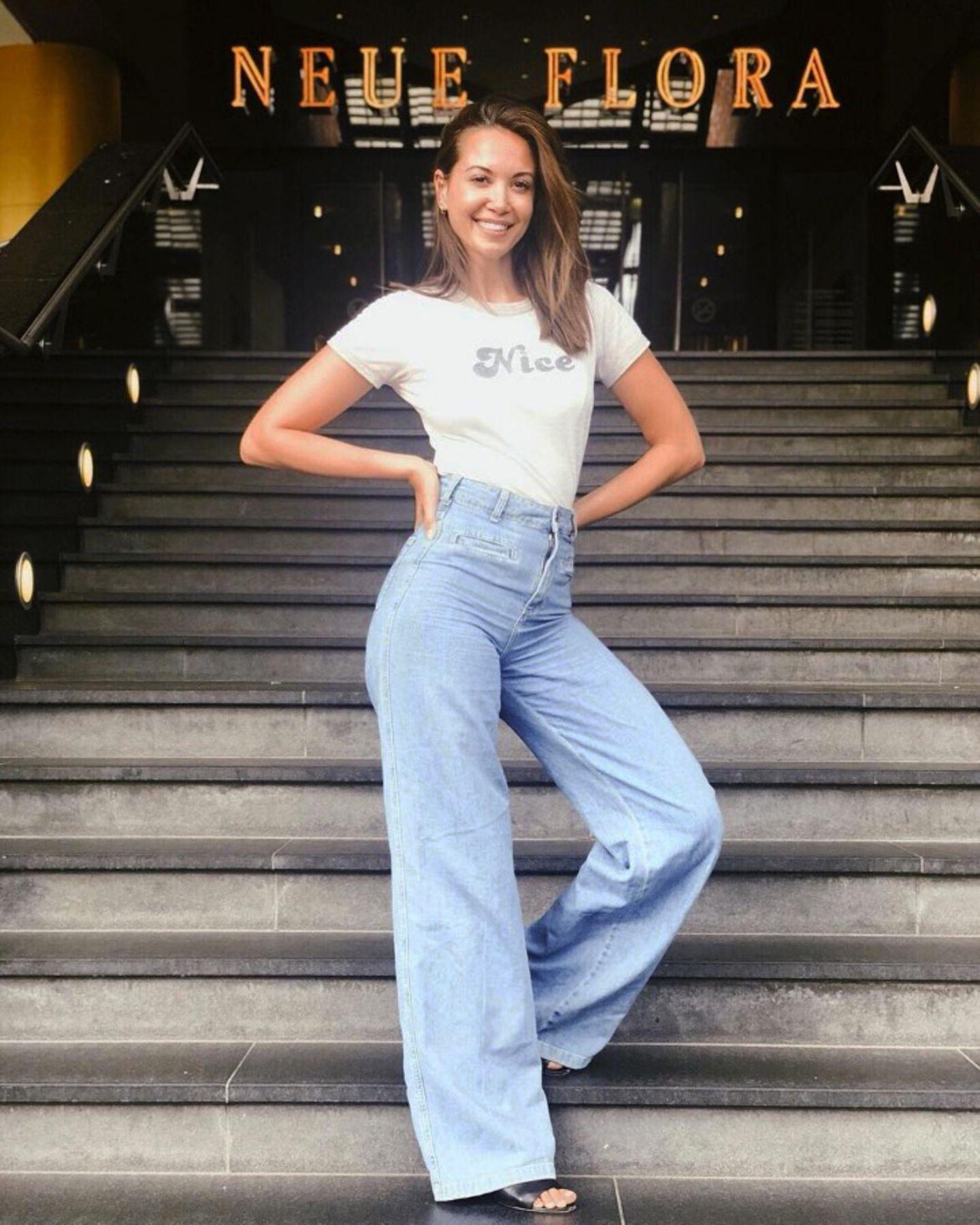 """""""Hamburg, jetzt gehöre ich erstmal dir ..."""" schreibt Grace Capristo zu diesem Foto auf Instagram. In den nächsten Wochen wird die Sängerin Prinzessin Jasmin im Musical Aladdin spielen und das findet Grace offenbar ziemlich """"nice"""" - zumindest verrät das ihr T-Shirt, welches sie mit einer High-Waist-Schlagjeans und einem tollen Lächeln kombiniert."""