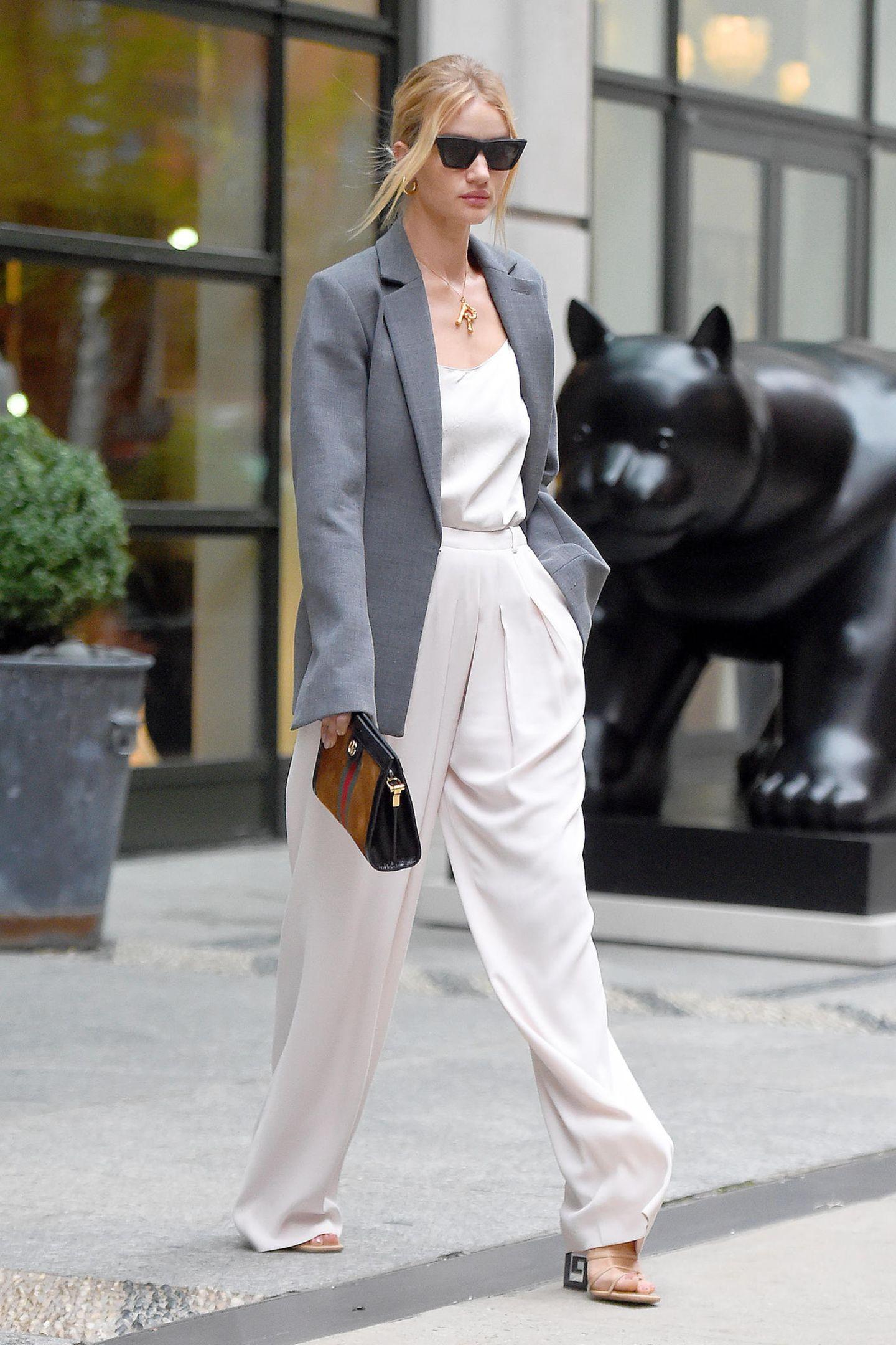 Was aussieht, wie ein Bild aus einer Fashion-Kampagne ist nur Rosie Huntington-Whiteley beim Verlassen ihres Hotels in New York. In einer weißen Marlene-Hose mit passendem Top, einem grauen Oversized-Blazer und mit cooler Sonnenbrille von Celine hat das Model ihren großen Auftritt.