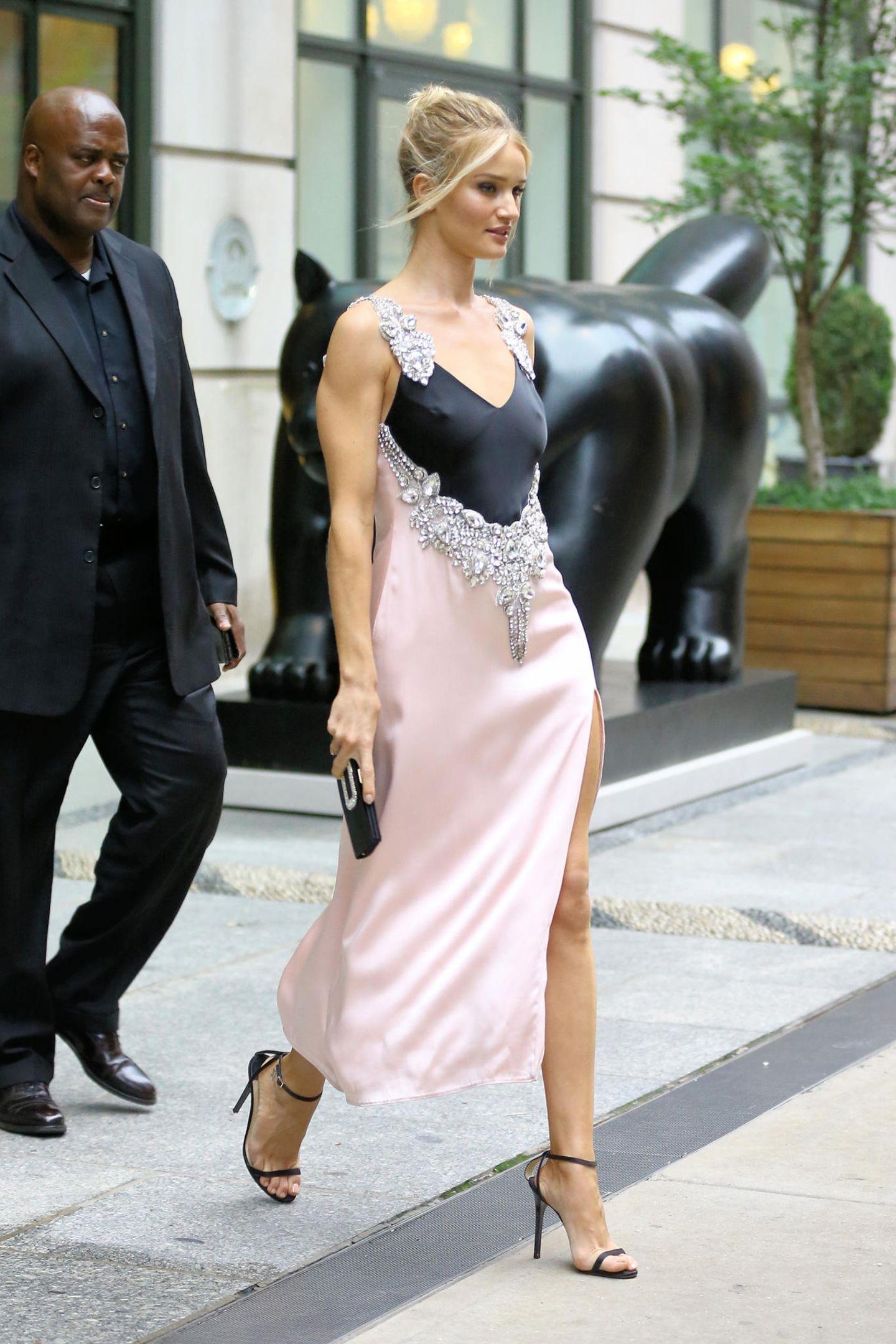 In einem seidenen Kleid mit Glitzerapplikationen schreitet Rosie Huntington-Whiteley in Begleitung ihres Bodyguards über die Straßen New Yorks. In der Hand hält sie eine schwarze Clutch und filigrane Riemchen-Heels strecken ihre Beine optisch.