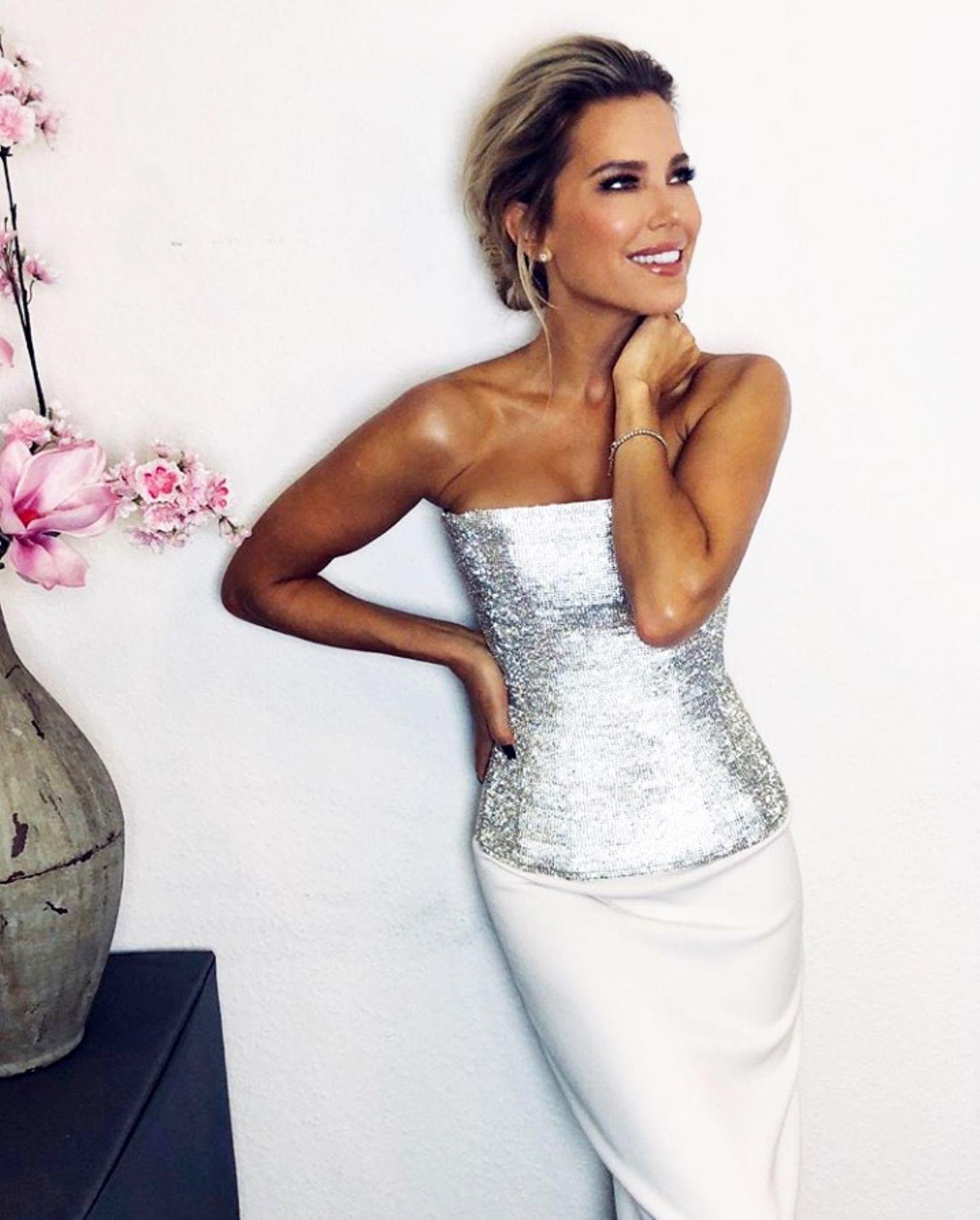 """Sylvie Meis strahlt mit ihren silbernen Pailletten um die Wette. Die sexy Korsage ist vom Label Lever Couture, der weiße, enge Rock von Amant Maitresse. Ein weiterer Look im Rahmen ihres Drehs für """"Das Supertalent""""."""