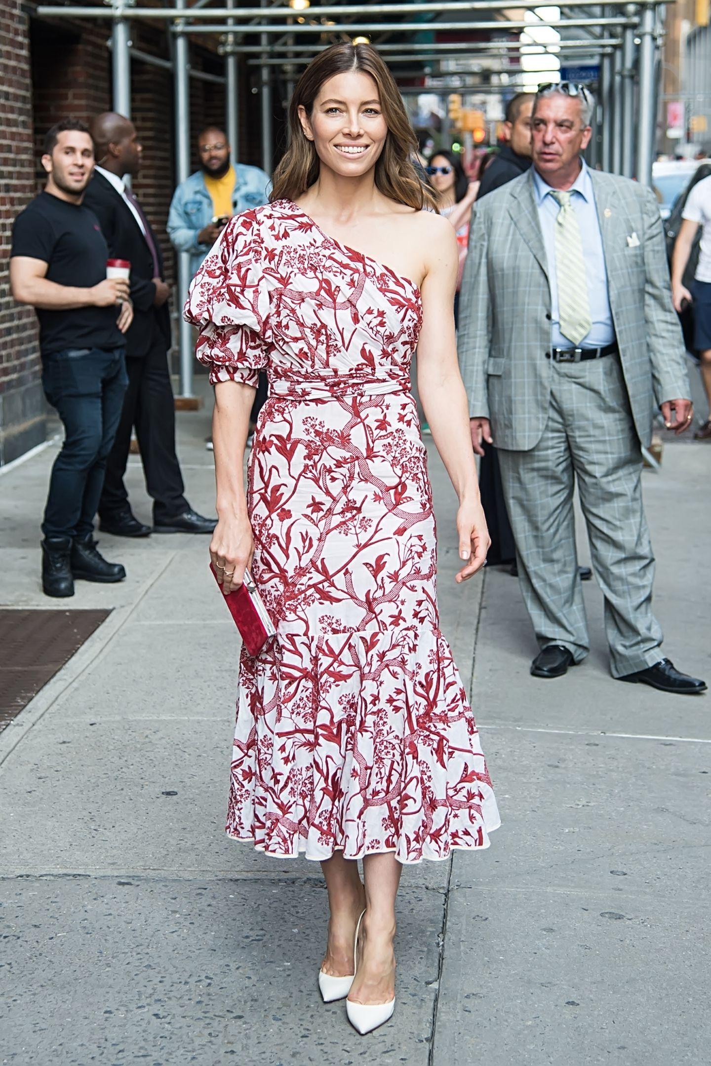 Der Twist zwischen klassischer Midi-Länge und modernem Print macht das Kleid zu einem echten Hingucker. Jessica kombiniert dazu eine rote Clutch und weiße Highheels von Christian Louboutin. Ein perfekter Look für die Schauspielerin, die damit ihre sportliche Figur perfekt in Szene setzt.