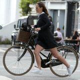 Beim rasanten Aufsteigen auf der Straße hängt der Helm am Lenker. In einem knappen schwarzen Kleid mit weißem Bübchenkragen schwingt sie sich auf das Fahrrad, auf dem sie so oft in London zu sehen ist.