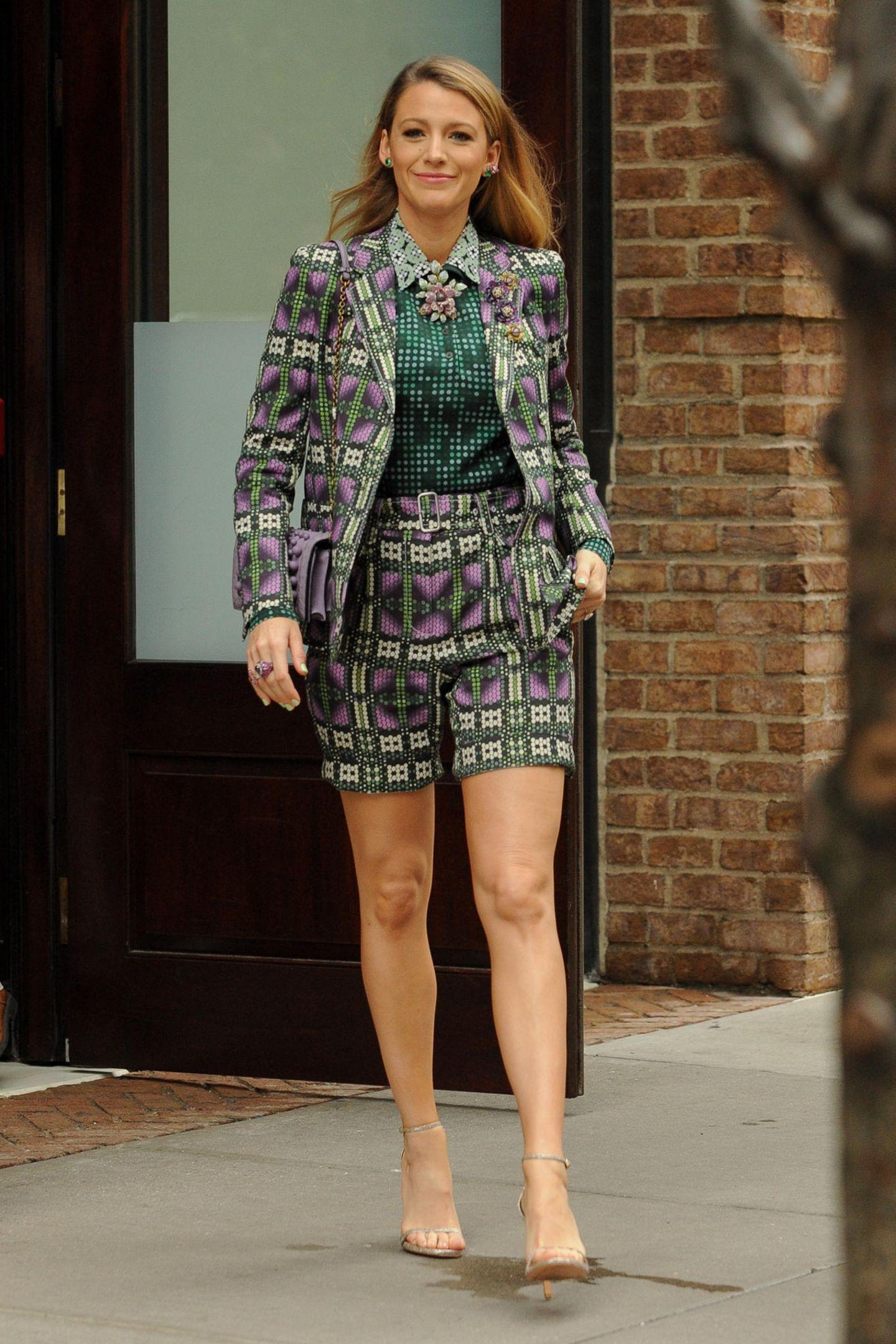 """In einem lila-grün gemusterten Anzug von Bottega Veneta präsentiert uns Blake Lively einen weiteren tollen Look aus der Kategorie """"Sie kann wirklich alles tragen"""". Während andere Damen vor den vielen Mustern und Farben zurückscheuen würden, legt sie einen absoluten Wow-Auftritt hin. Die hellen Riemchen-Heels von Stuart Weitzman strecken das Bein optisch."""