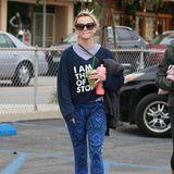 Reese Witherspoon mixt ganz schön wild: Zum Slogan-Sweater kommt bei ihr eine Hose mit Aztekenmuster und Sneaker mit Neon-Schnürsenkeln.
