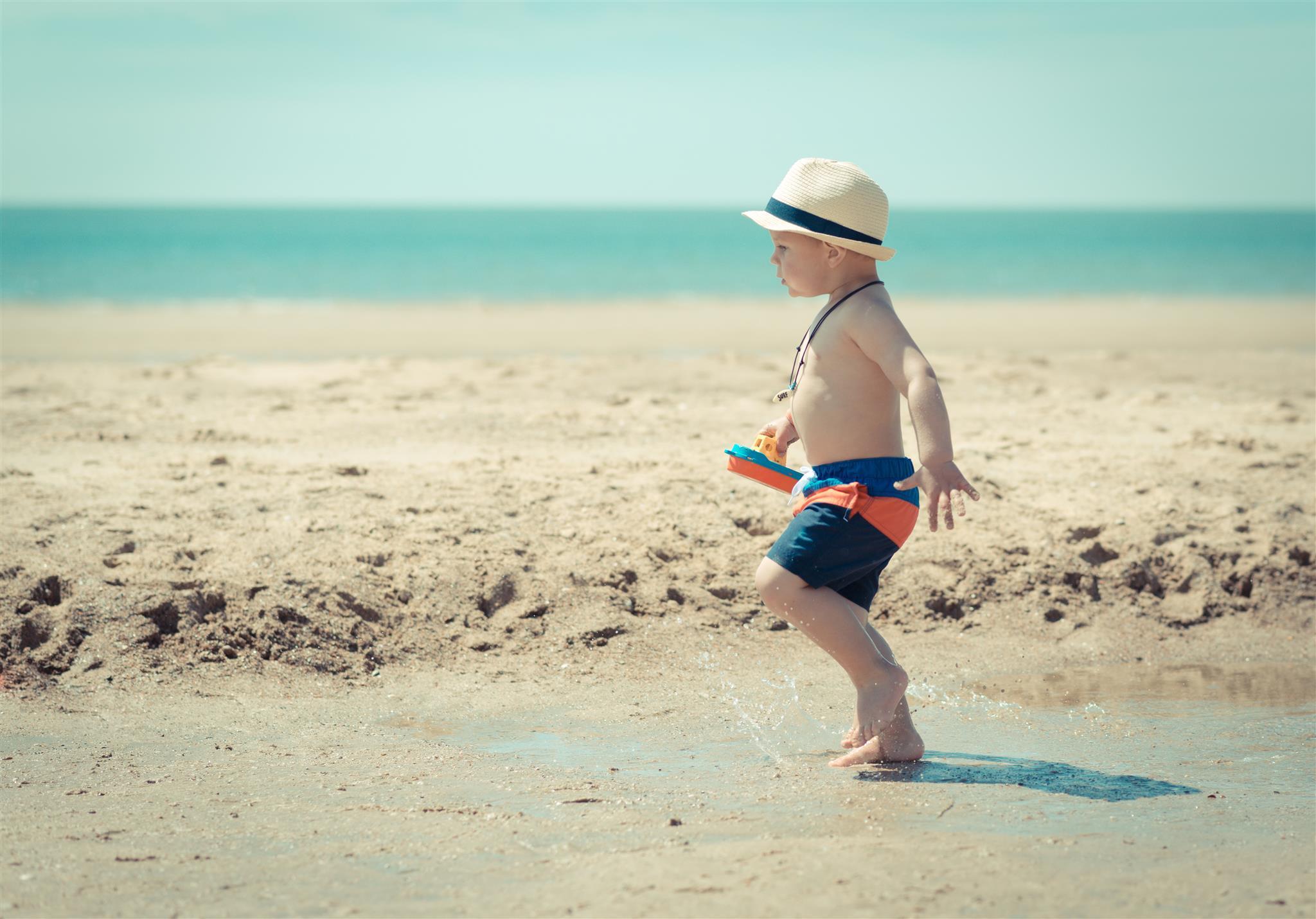 Junge spielt am Strand (Symbolbild)