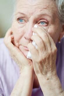 Symbolbild: Eine ältere Frau trocknet ihre Tränen.