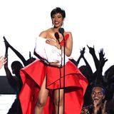 """Im ausladenden Satin-Dress bringt die frischgebackene Mama Cardi B ihr """"Baby"""" mit auf die Bühne, natürlich ein Scherz, sie nimmt nur das Publikum auf den Arm."""
