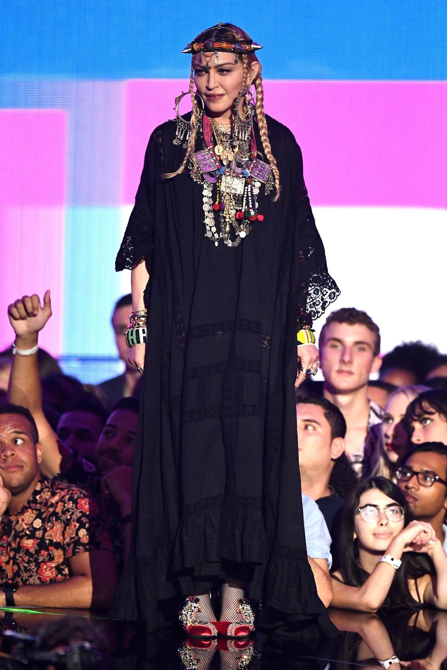 Dafür ist der Rest ihres Outfits, der schwarze Spitzen-Kaftan, eher unauffällig. Madonnas Schuhwerk ist dafür wieder ein Blickfang.