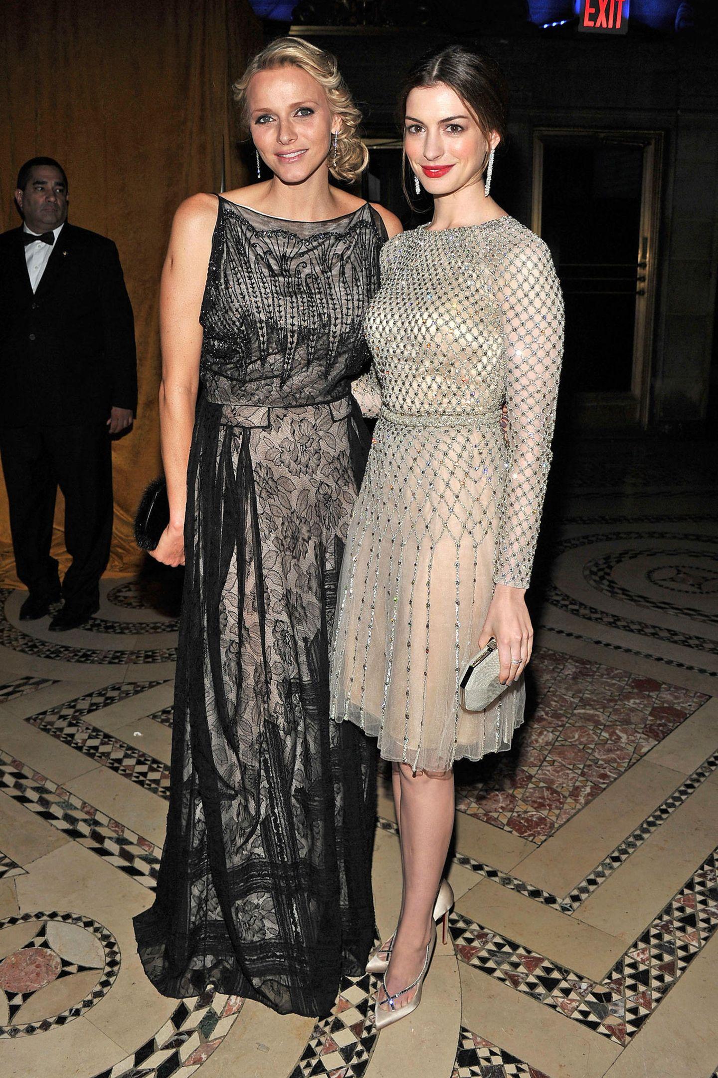 In metallischen Glamour-Look treffenCharlène vonMonaco und Anne Hathaway bei derPrincess Grace Awards Gala im November 2011 in New York aufeinander