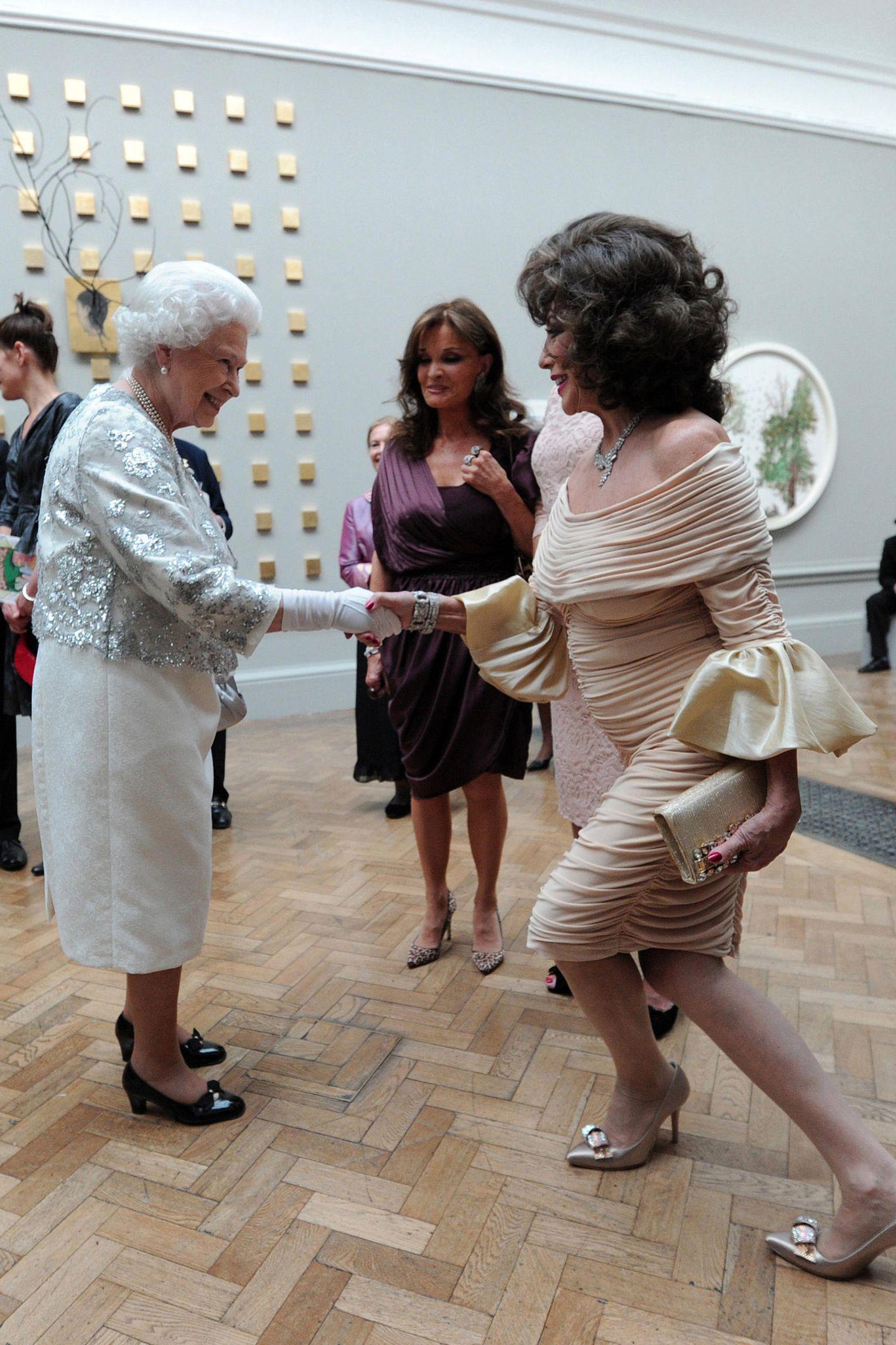 Joan Collins knickst beim Treffen mit Queen Elizabeth in der Royal Academy of Arts 2012 so tief, wie es ihr schulterfreies Cocktailkleid in Beige erlaubt.
