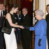 Eine strahlende Gemma Arterton im Schwarz-Weiß-Look wird im Februar 2014 von der Queen höchstpersönlich im Buckingham Palast empfangen.