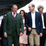 """""""Paddington""""-Star Hugh Bonnevilles waldgrüner Dreiteiler mit pinkfarbener Krawatte stiehlt Prinz William beim Besuch der Paddington Station im Oktober 2017 glatt die Show."""