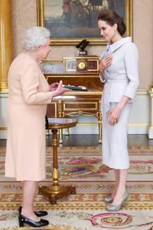 """Im eleganten, beigefarbenen Kostüm von Ralph & Russo wird Angelina Jolie von Queen Elizabeth im Oktober 2014 ehrenhalber zur """"Dame"""" im Orden von Saint Michael und Saint George ernannt. Eine große Ehre für den engagierten Hollywood-Star und entsprechend gewürdigt mit diesem tollen Look."""