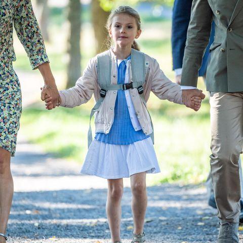 Am Tag ihrer Einschulung zeigtsich Prinzessin Estelle von ihrer besten Seite. Zum weißen Röckchen trägt sie ein Plissé-Oberteil mit Bubi-Kragen und eine weiße leichte Strickjacke. Cooler wird der Schulmädchenlook durch eine Bomberjacke.