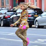 """Die Schauspielerin dreht eine Pirouette und lässt dabei ihre Haare fliegen. Zum Mustermix im Pyjama-Stil von """"Intimissimi"""" kombiniert Sarah Jessica Parker pinkfarbeneAccessoires in Form einer Clutch und spitzen Pumps. Ein echter Hingucker!"""