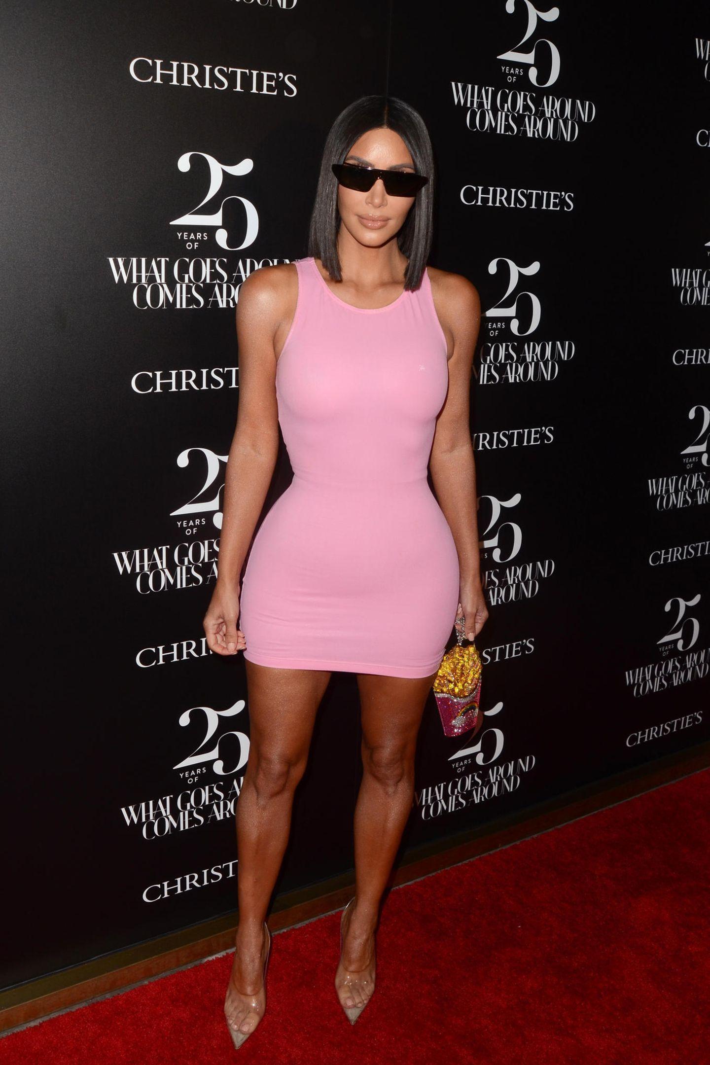 """Kurz zuvor sitzt das bonbonfarbene Mini-Dress vom Kim Kim Kardashian noch perfekt. Seelenruhig posiert sie für die Fotografen der """"What Goes Around Comes Around""""-Party in Los Angeles und setzt ihren kurvigen Körper in Szene. Übrigens: Die coole Pommes-Tasche von Designerin Judith Leiber ist für schlappe 5.700 Euro sogar noch zu haben!"""