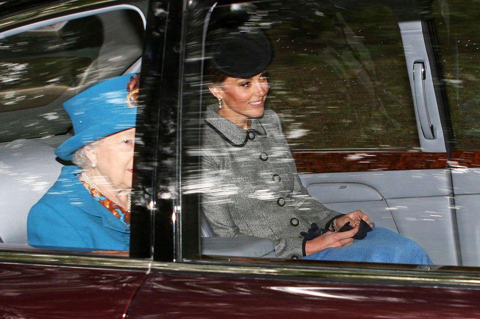 Neben der Queen in leuchtendem Blau gibt sich Catherine ganz zurückhaltend im eleganten, grauen Kostüm. Die himmelblaue Decke über ihren royalen Knien überrascht uns aber wirklich, schließlich sollte das Luxusauto ausreichend beheizt sein. Wirst du etwas älter, Kate?