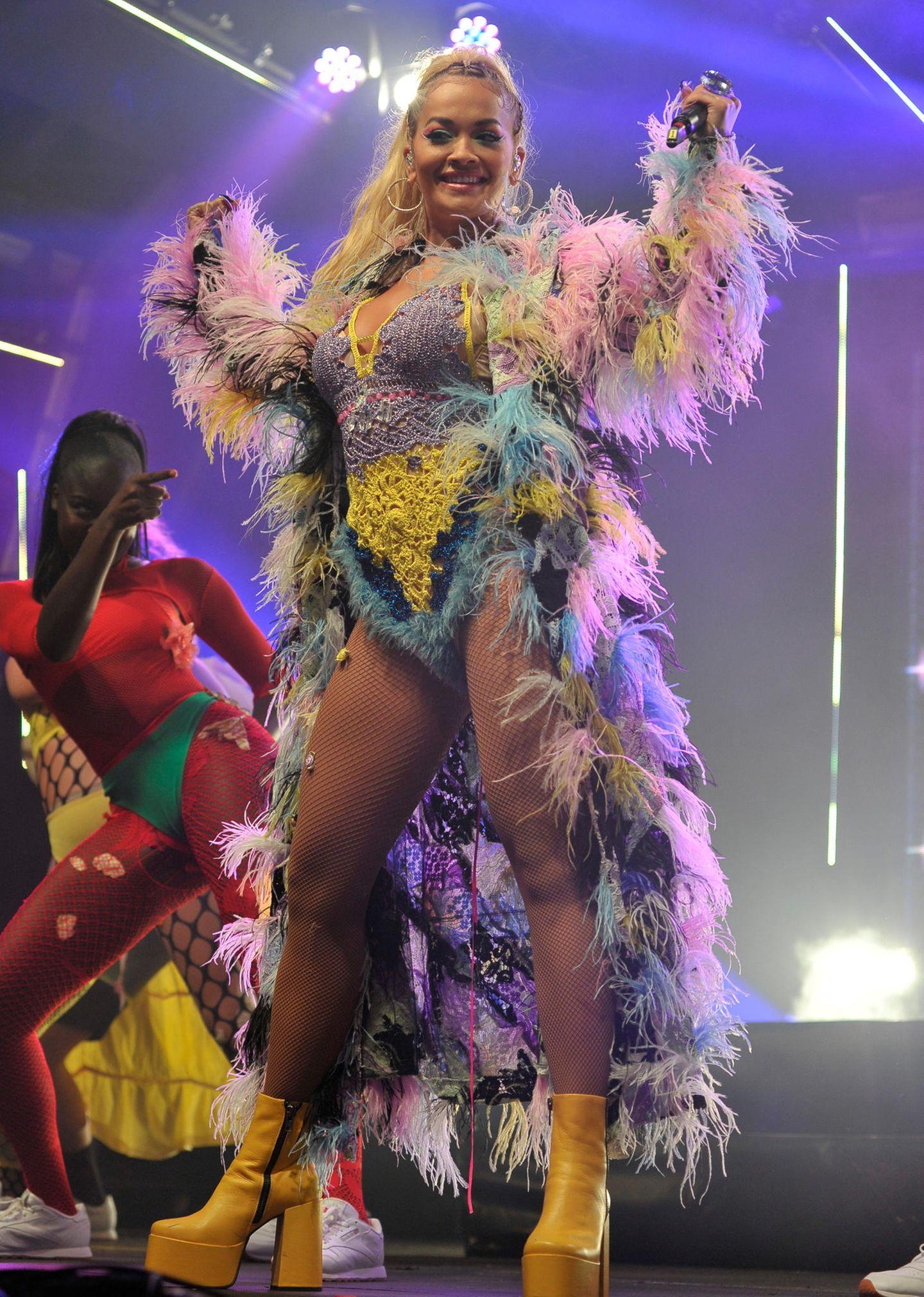Egal ob beim Streetstyle oder beim Bühnenlook: Sängerin Rita Ora mag es gerne flippig! Beim Manchester Pride Festival überrascht sie ihre Fans mit einem ausgeflippten, bunten Feder-Umhang, ebenfalls bunten Häkel-Body, einer sexy Netzstrumpfhose undgelben Plateau-Schuhen von Naked Wolfe. Dieses Outfit eignetsich einfach wunderbar zum ...