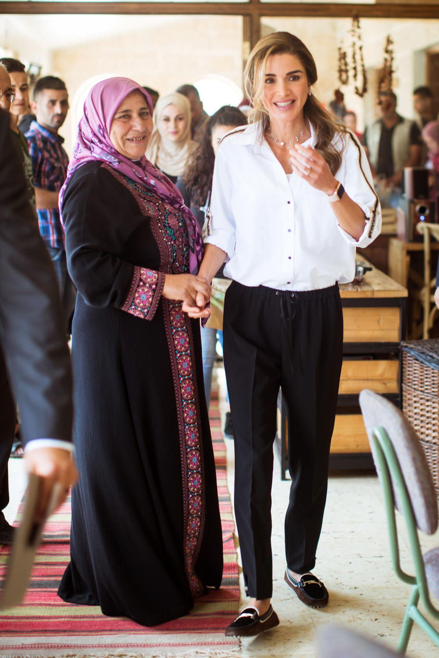 Königin Ranja besucht Projekte der Cooperative Society Al Kifahin Ailjoun und wählt dafür einen perfekten Look. Zu einer schwarzen, legeren Stoffhose trägt sie eine weiße Bluse von Zara und klassische Loafer von Tod's. Eine wirklich gelungene Mischung aus günstig geshoppt und luxuriös.