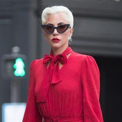 """Wow, was für eine Lady in Red spaziert denn hier durch die Straßen von Paris? Keine Geringere als Sängerin Lady GaGa. Ihr stylishes Midi-Kleid mit Schleifen-Applikation am Hals stammt von dem amerikanischen Label """"CO"""". Zum Kleidkombiniert die Sängerin eine Cat-Eye-Brille im 60's Lookund schwarze klassische Pumps - très chic!"""