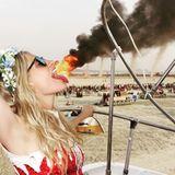 """Model Poppy Delevingne überrascht Fans mit einem Throwback-Foto von ihr, auf dem es scheint, als würde sie Feuer speien. Auch wenn die Täuschung äußerst geschickt ist, tut Cara Delevingnes Schwester das natürlich nicht. Die schöne Blondine hat sich bloß im gekonnten Winkel vor einweit entferntes Feuer bei dem Event """"Burning Man"""" gestellt."""