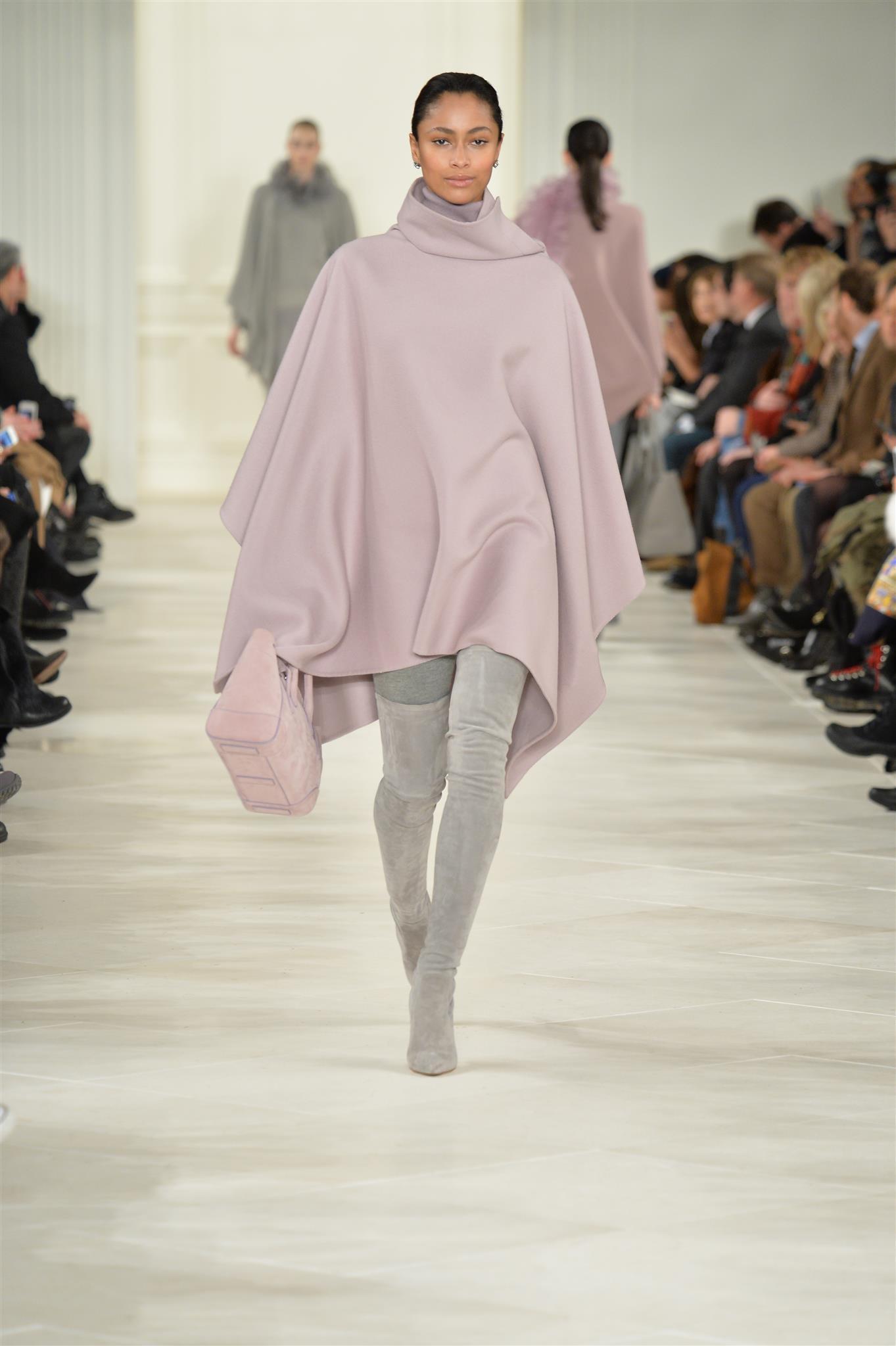 Ein Model mit einem Poncho auf dem Laufsteg.