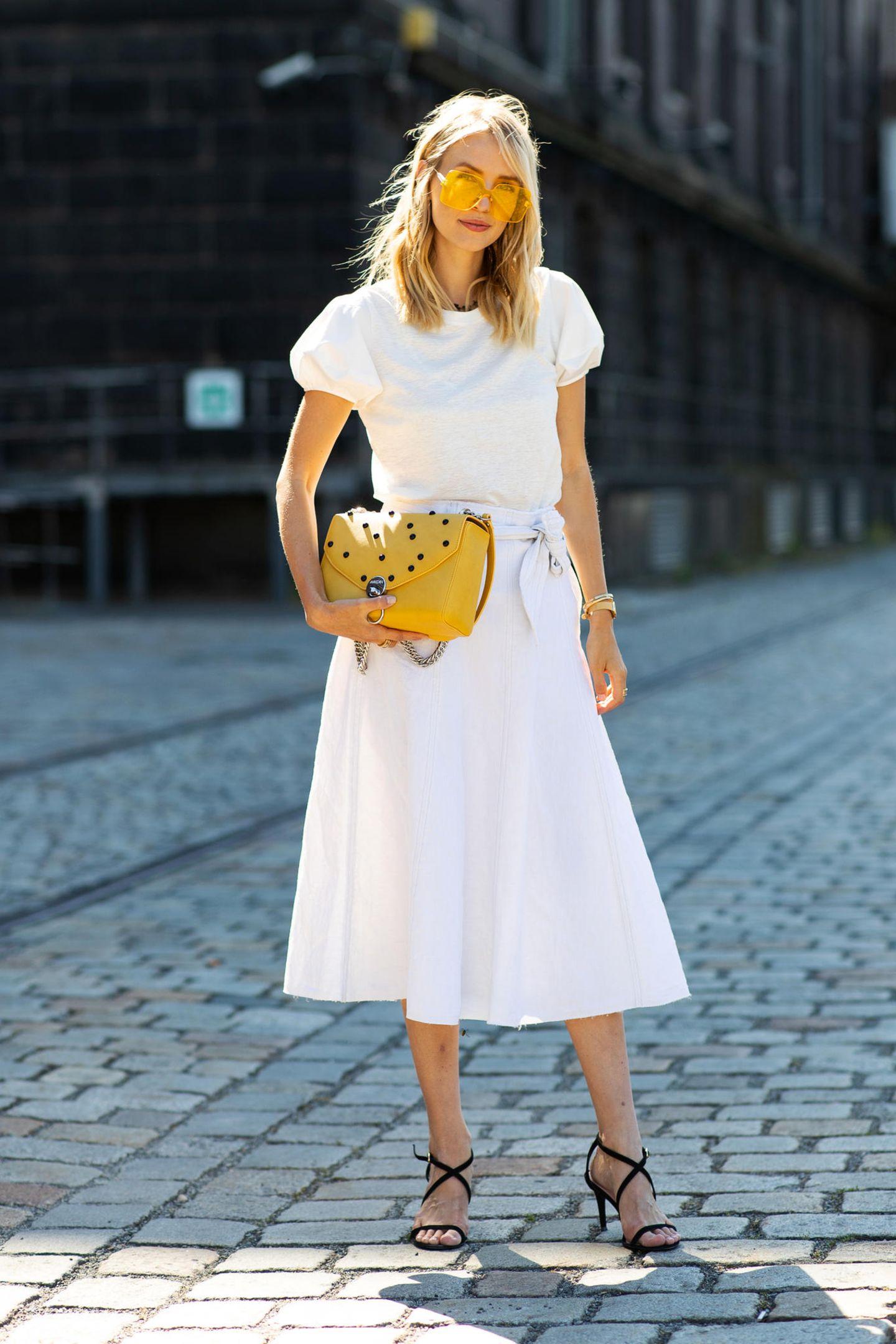 Akzente setzen: Bloggerin Leonie Hanne strahlt mit ihren gelben Accessoires mit der Sonne um die Wette. Zum All-White-Look kombiniert sie eine coole It-Bag von Marc Cain mit einer farblich passenden Sonnenbrille.