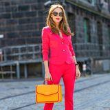 Color Blocking: Bloggerin Alexandra Lapp kombiniert zu einem pinkfarbenen Hosenanzug eine orangefarbene Handtasche und beweist, dass Mut zur Farbe sich lohnen kann.