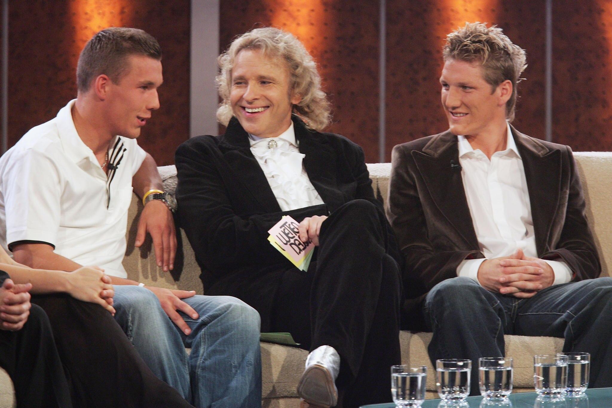 """Lukas Podolski (l.) und Bastian Schweinsteiger (r.) unterhielten die Zuschauer nicht nur mit sportlichen Top-Leistungen, sondern auch mit viel Humor und guter Laune abseits des Fußballfeldes. Hier im Oktober 2005 auf der Couch des damaligen """"Wetten, dass...""""-Moderators Thomas Gottschalk"""