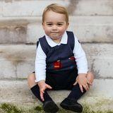 """Auf den offiziellen Weihnachtsfotos begeistert der damals 16 Monate alte Prinz seine Fans. Mit roten Bäckchen undlässigem Seitenscheitel lächelt er verschmitzt in die Kamera. Sein Outfit? Klassisch! Hellblaues Hemd, dunkelblauer Pullunder mit Stickereien (von """"Cath Kidston""""), Shorts, Kniestümpfe und Schuhe sind perfekt aufeinander abgestimmt. Für viele andere Kinder seines Alters könnte es jedoch schwer gewesen sein, die Festtage in dem kuschelig warmen Überzieher zu zelebrieren. Nach nur einer Woche war das Oberteil restlos ausverkauft."""