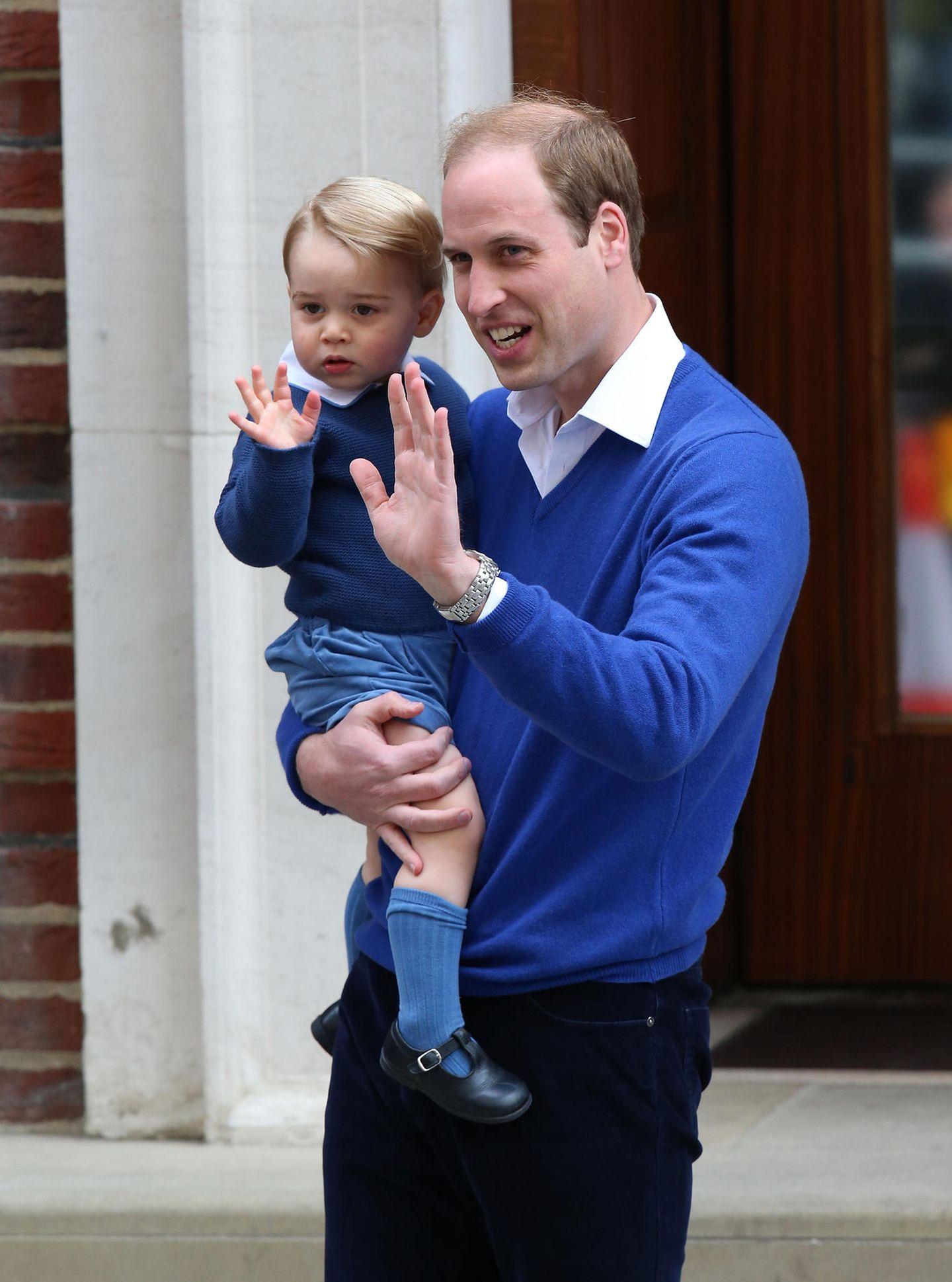 Mai 2015: Wie der Vater, so der Sohn: Prinz George besucht seine frisch geborene Schwester im Lindo Wing in London. Perfekt abgestimmt auf Daddys Outfit, trägt auch Georgeeinen blauen Wollpullover mit Kragen, sowie dunkelblaue Shorts, Strümpfe und Schuhe. Ein Klassiker-Look, der viele Nachahmer gefunden hat.