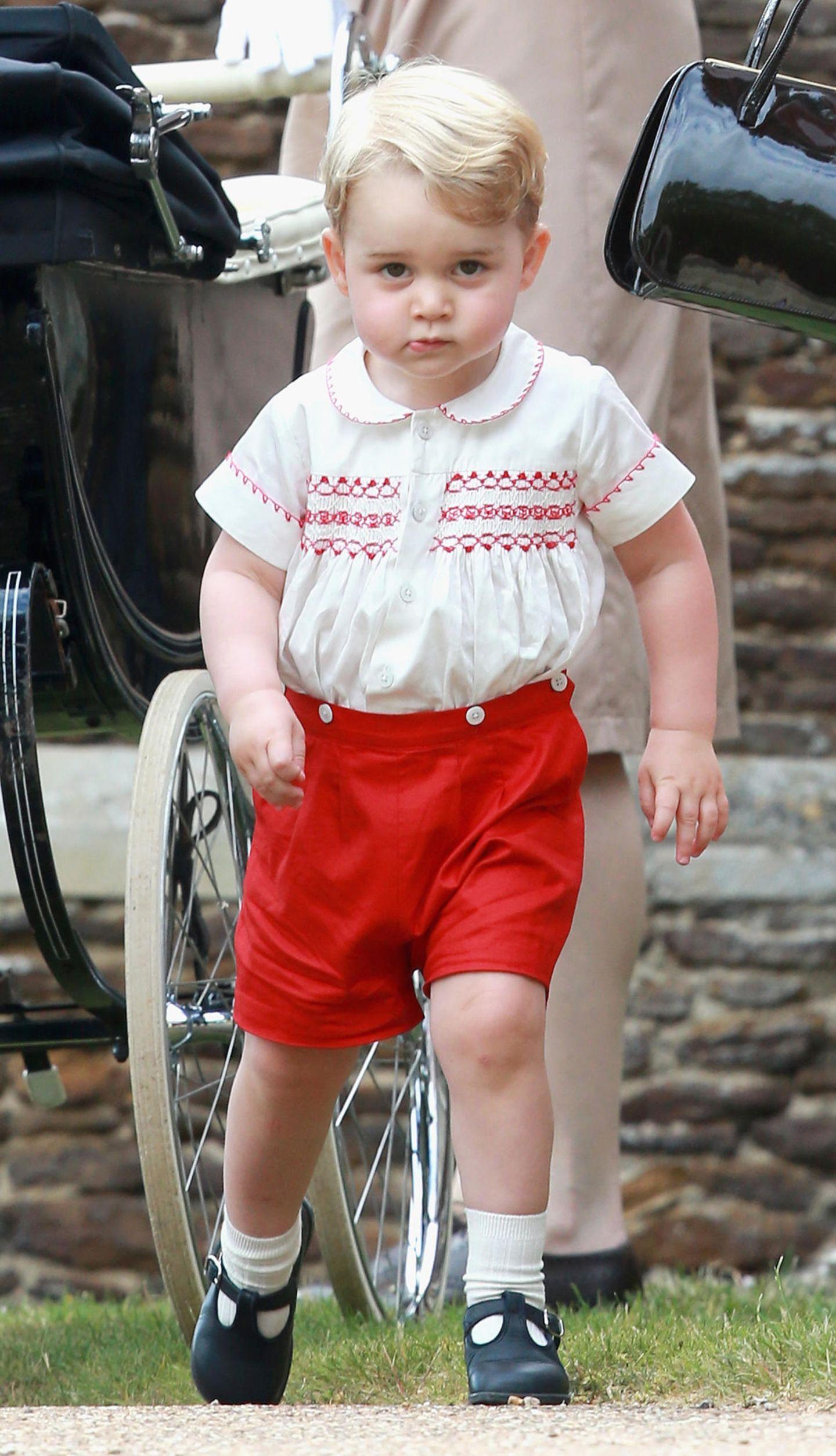 """Mai 2015: Zur Taufe seiner Schwester Prinzessin Charlotte entzückt George in einer roten Shorts und einer Bluse mit passenden, roten Stickereien der britischen Marke """"Rachel Riley"""", die auf traditionelle Kleidung spezialisiert ist. Aufmerksame Royal-Fans haben schnell festgestellt: Ein ähnliches Outfit trug bereits sein Vater Prinz William, als er 1984 seinen Bruder Prinz Harry im Krankenhaus besuchte."""