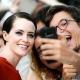 Die britische Schauspielerin Claire Foy schießt ein Selfie mit Fans auf dem Roten Teppich.