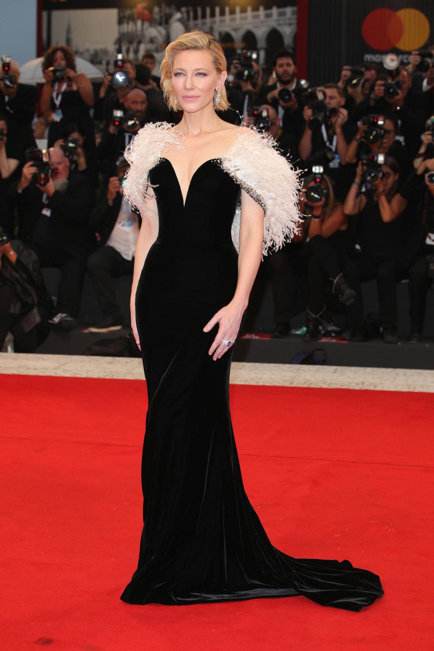 Cate Blanchett trägt eine schwarze, bodenlange Robe mit tiefem Ausschnitt. Über die Schultern fällt ihr eine Federstola in einem hellen Rosaton.
