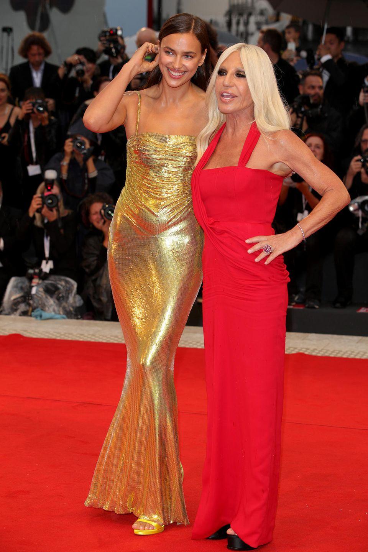 Während Irinas Partner, Bradley Cooper, mit seiner Filmkollegin Lady Gaga über den roten Teppich schreitet, wird sie an diesem Abend von Donatella Versace begleitet. In einer engen, goldenen Robe zieht sie alle Blicke auf sich. Donatella wählt ein knallrotes Kleid mit Knoten-Details - beide stammen natürlich aus dem Hause Versace.