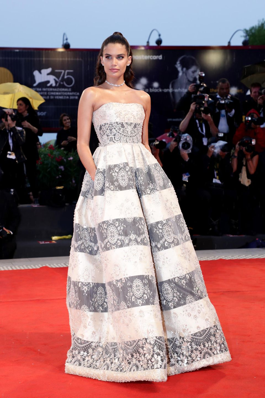 Sara Sampaio begeistert in einem gestreiften Kleid mit Spitzenüberzug. Dazu trägt sie einen Half-Bun und edlen Schmuck.