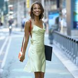 Hannah Donker zeigt ihre Topfigur in einem Seidenkleid mit filigranen Trägern. Ihre Modelmappe trägt sie lässig unterm Arm. Nudefarbene Pumps runden den Look ab.