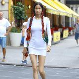 Das nepalesische ModelVarsha Thapa begeistert in einem schlichten weißen Kleid und mit aufwendigem Haarschmuck. Schwarze Riemchen-Heels runden den Look ab.