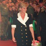 Lady Diana zeigt in ihrem Blazer-Dress mit weißem Revers und goldenen Knöpfen nicht ganz so viel Bein. Auch sie entscheidet sich für nackte Beine und Pumps. Ob Meghan sich bei der Outfitwahl an der verstorbenen Prinzessin orientiert hat?