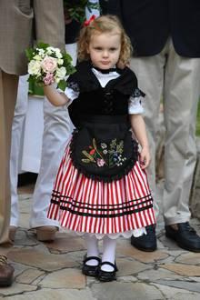 Prinzessin Gabriella trägt zu ihrem rot-weiß-gestreiften Kleidchen mit weißem Spitzenunterrock einen schwarzen Spitzenüberzug mit Schürze. Trotz sommerlicher 25 Grad trägt der Mini-Royal eine weiße Strumpfhose. Das rote Schleifchen in ihren blonden Löckchen macht den Look perfekt.